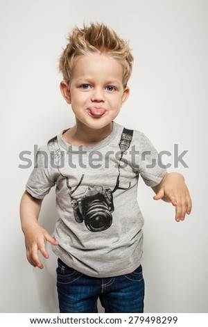 Naughty boy making a grimace and sticking his tongue out. Studio portrait over white background - stock photo