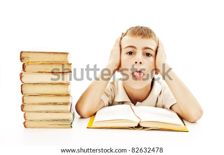 Naughty child sticks out his tongue with school books on the table - stock photo
