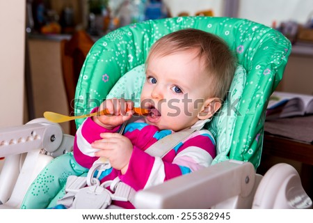 Naughty cute baby eating alone in the high chair - stock photo