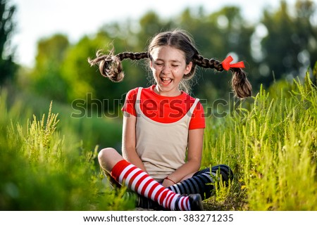 naughty girl with pigtails, opens his mouth and shouts, the summer on the nature - stock photo