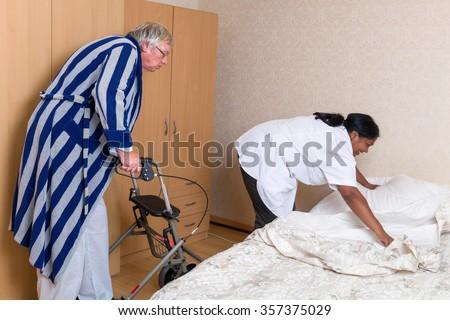 Naughty grandpa in nursing home admiring the nurse's butt - stock photo