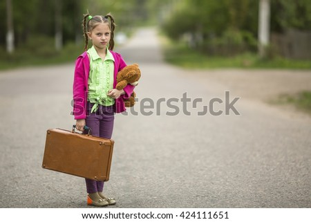 Naughty little girl with a suitcase and a Teddy bear is going on a trip. - stock photo