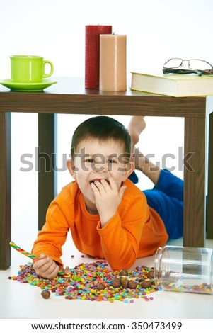 Naughty little kid eating sweets under table. Smiling, isolated on white, lollipop in hand. - stock photo