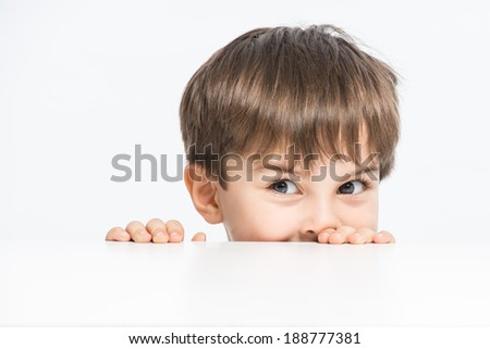 Naughty little spy peek a boo, with curious eyes kilroy, close up - stock photo