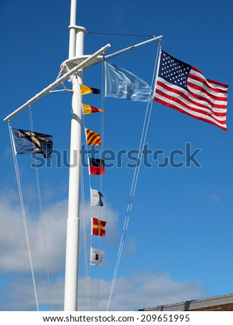 Nautical and American Flags Flying from a Ship's Mast with Wispy Clouds and Blue Sky - stock photo