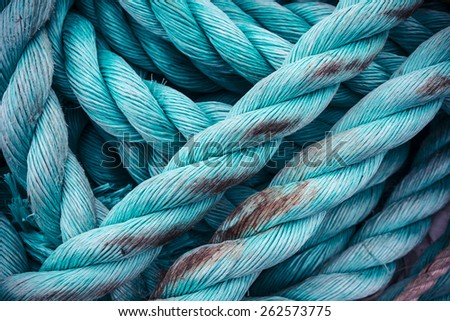 Nautical background. Closeup of an old blue frayed boat rope. Tonned image. - stock photo