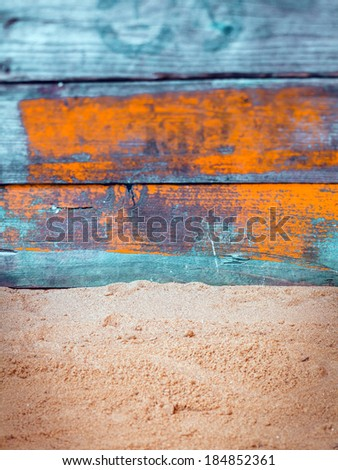 Nautical background with weathered blue and orange painted wooden boards above golden beach sand in vertical format - stock photo