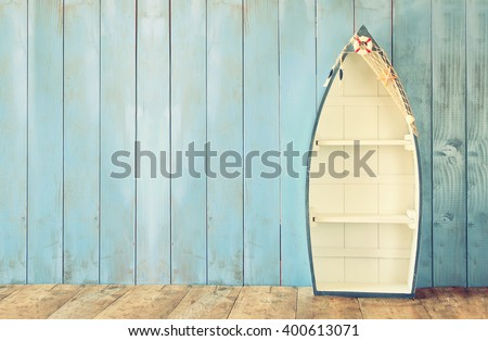 nautical boat shape shelves on wooden table. product display background, vintage filtered - stock photo