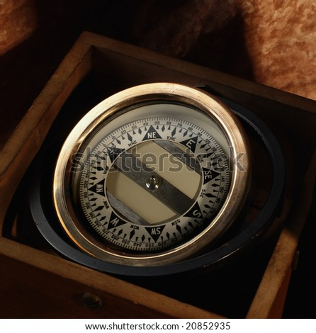 Nautical compass in a wooden box on brown background