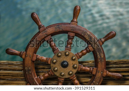 Nautical Detail Of A Ship's Wheel Against Tropical Ocean Water - stock photo