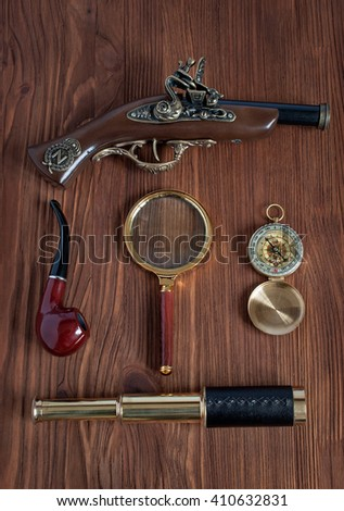 Nautical flat lay collection with pistol, compass, spyglass,  magnifying glass and smoking pipe - stock photo