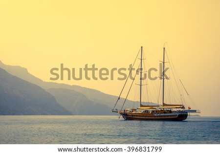 Nautical landscape with retro sailboat at sunset. Sea voyage on sailing yacht - luxury lifestyle in summer. Seashore with sailing vessel near islands, soft light effect.  - stock photo