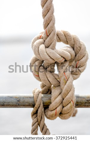 Nautical rope and knot close up on a sailboat at sea with a cloudy background - stock photo