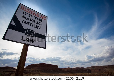 Navajo sign saying Buckle up - it's a Navajo Nation Law - against the sky - stock photo