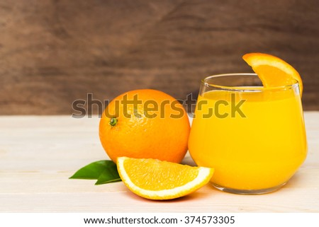 Navel orange juice and slices of orange with leaves on wooden background - stock photo