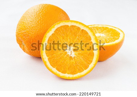 Navel orange seedless Fruits on white Tablecloth, Fresh juicy Organic orange with a second fruit at the apex visible - stock photo