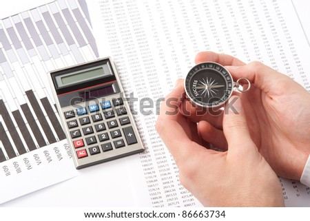 Navigate to success in business and compare right direction in business concept. Man with compass directed to success word. Calculator, sheet and graph represent business. - stock photo