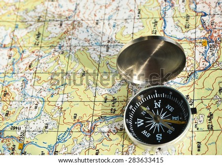 Navigation equipment for orienteering. Magnetic compass and topographic map.