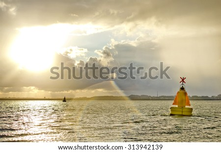 Navigation Marker, indicating a hazard in a shipping lane during a cloudy sunrise with variable weather - stock photo
