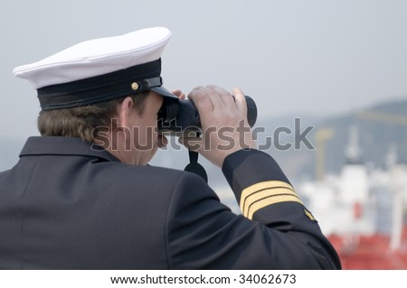 Navigation officer with binocular, looking ahead on the navigation bridge of ocean ship