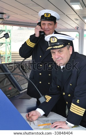 Navigation officers manages devices, looking ahead on the navigation bridge of ocean ship - stock photo