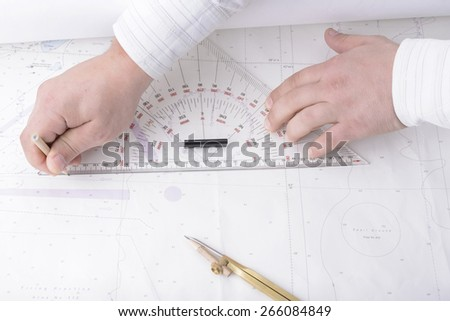 navigator hands are drawing ship track on navigation map - stock photo