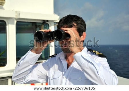 navigator on navigation bridge during his watch on seagoing vessel with binocular - stock photo