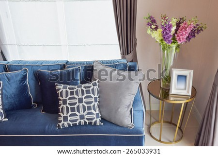 Navy blue classic sofa and retro pillows with a lovely orchid vase on side table in living corner - stock photo