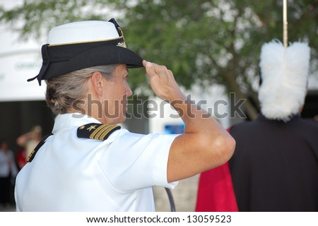 Navy Commander saluting flag at Memorial Day ceremony - stock photo