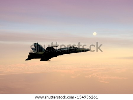 Navy jetfighter flying at high altitude before sunrise