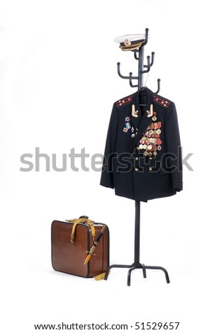 Navy officer's coat with military medals and old suitcase - stock photo