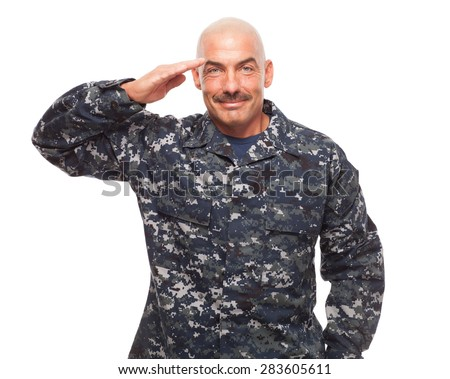 Navy sailor or chief grinning while saluting on white background. - stock photo