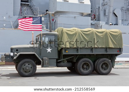 Navy ship sits in the background behind a military truck.