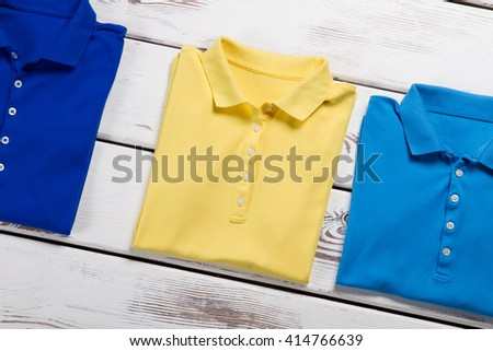 Navy, yellow and blue t-shirts. Polo t-shirts on wooden background. Special offer at local store. Selection of woman's summer clothes. - stock photo