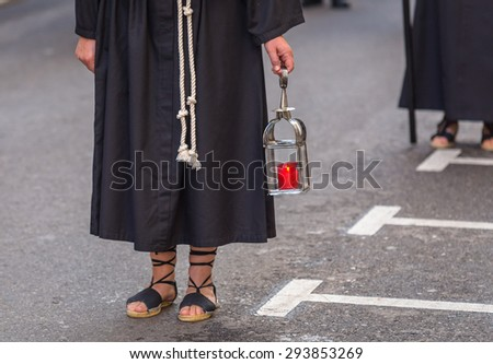 Nazareno carrying a candle holder in the Good Thursday during Holy Week in Valladolid. - stock photo
