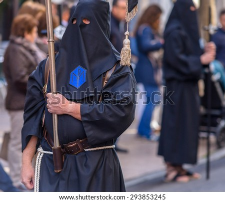 Nazareno in black carrying a flag during Holy Week in Valladolid. - stock photo