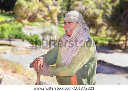 NAZARETH, ISRAEL - APRIL 24: Man dressed as a first-century herder tends his flock at Nazareth Village, a representation of life at the time of Jesus in Nazareth, Israel, Apr 24, 2012 - stock photo
