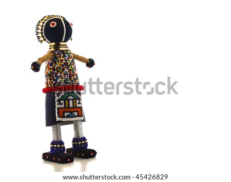 Ndebele Maiden Doll on white background. The Ndebele are an african tribe. The apron on this doll signifies that the girl has undergone her puberty rites and is now of marriageable age. - stock photo