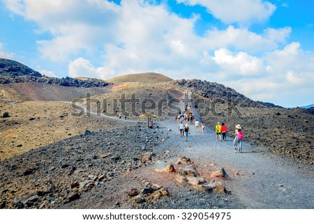 NEA KAMENI, SANTORINI, GREECE- OCTOBER 5, 2015: Hiking group of tourists on volcanic island Nea Kameni. The uninhabited volcanic island in Aegean sea, Mediterranean, Greece.