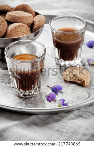 Neapolitan style coffee. Espresso in two shot glasses, with almond biscuits, on silver tray. Toned photo. - stock photo