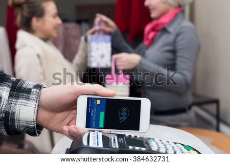Near Field Communication - Man completing mobile Payment Woman shopping, male Hand holding cell Phone making instant Transaction at Store checkout Terminal Saleswoman and female Consumer on Background - stock photo