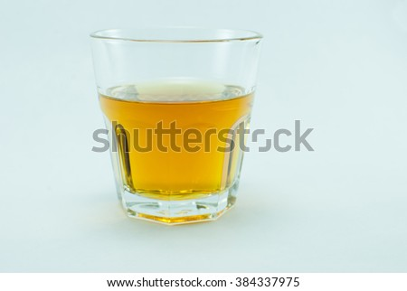 Near full glass of whiskey standing towards white background.