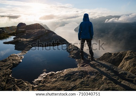 Near Preikestolen (Pulpit Rock), the famous tourist attraction in Ryfylke, towers over the Lysefjord. Guy on a rock looks into the distance and enjoys the dawn