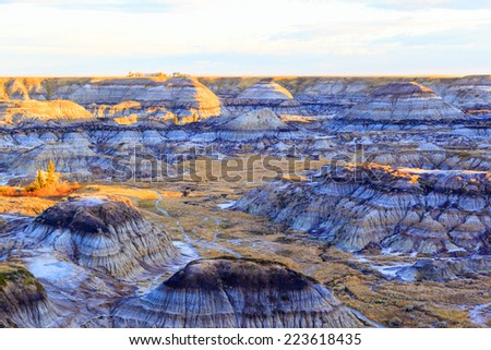 Near sunrise over the Drumheller badlands at the Dinosaur Provincial Park in Alberta, where rich deposits of fossils and dinosaur bones have been found. The park is now an UNESCO World Heritage Site. - stock photo