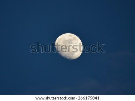 Nearly full moon on twilight - stock photo