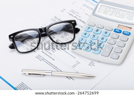 Neat calculator with pen, glasses and utility bill under it