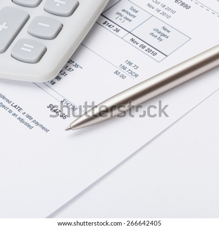 Neat calculator with silver pen and utility bill under it - close up shot - stock photo