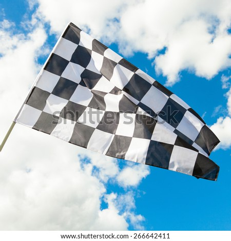 Neat checkered flag with cumulus clouds behind it - stock photo