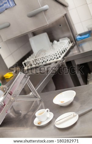 Neat interior of a commercial kitchen with wall mounted utensils and a range of different stainless steel pots arranged on a central gas hob - stock photo
