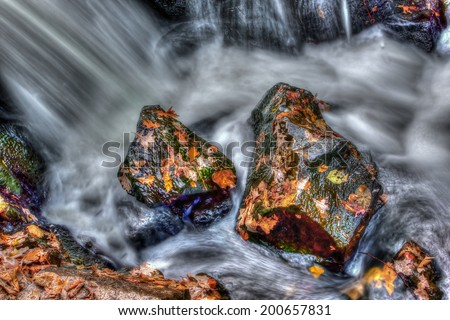 Neat looking rocks and leaves with smooth water running by in high dynamic range - stock photo